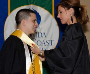 Photo is of Andres Machado receiving his Honors sash from Service-Learning Director Jessica Rhea