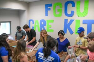 Photo shows FGCU students assembling care kits for Hurricane Irma shelters.