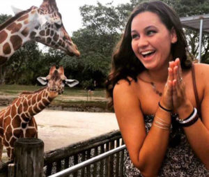 Photo shows FGCU student with giraffes she studied