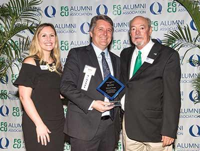 Kim Wallace, director of Alumni Relations, 2018 Alumnus of Distinction winner Michael Wynn and FGCU President Mike Martin.