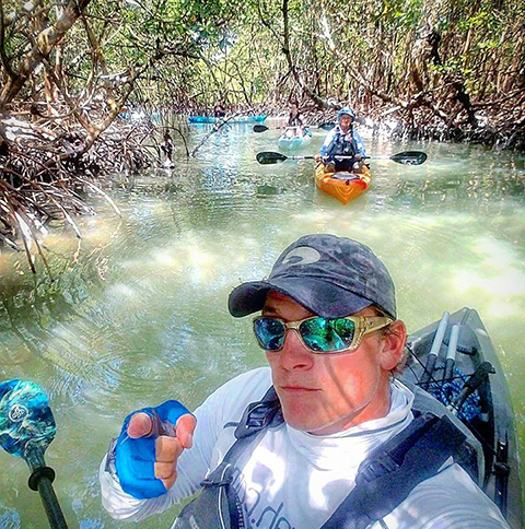 Photo shows Ryan Young leading a kayak tour
