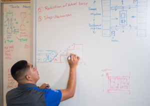 Photo shows students drawing on whiteboard