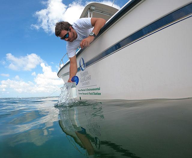 Photo shows FGCU researcher taking water sample in Florida Keys