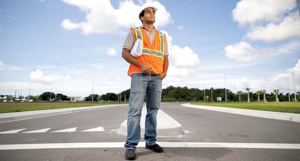Photo of Angel Hernandez standing and staring off from roadway intersection.