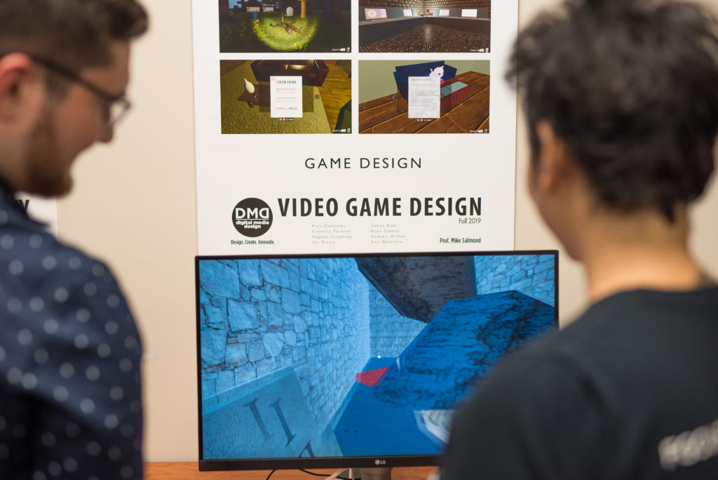 Photo shows students looking at a video game on a screen.
