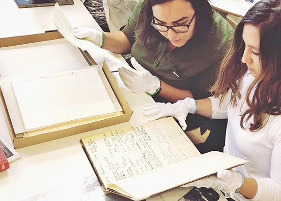 Photo shows FGCU students looking at historical documents