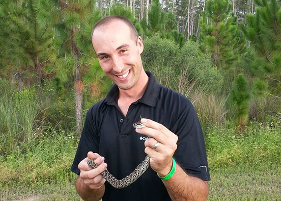 Photo shows professor holding snake