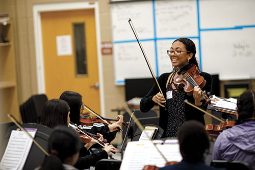 Violin player leading class.