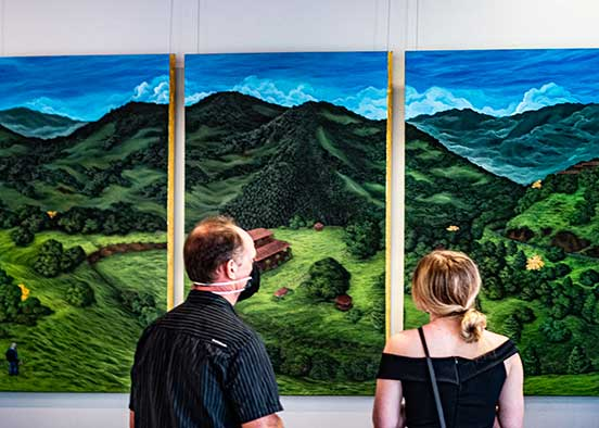 Photo shows people looking at artwork