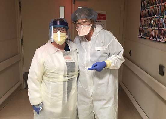 PHoto shows nurses in protective gear