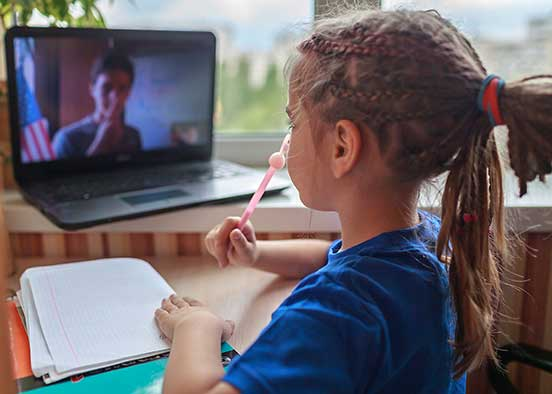 Photo shows girl learning remotely on laptop