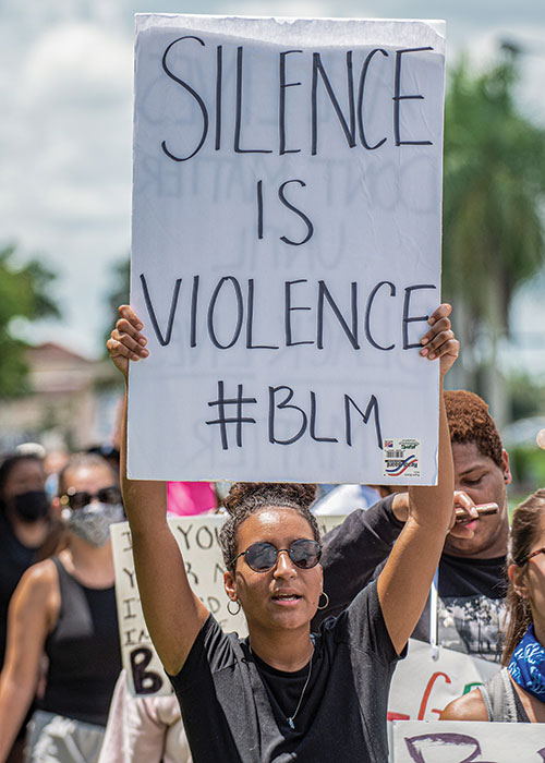 Student with sign that reads Silence is Violence #BLM