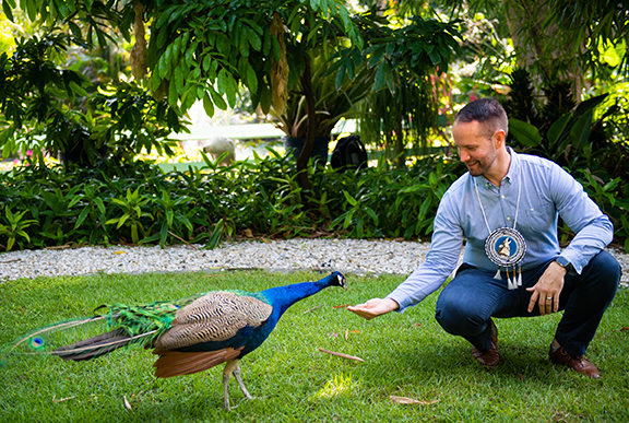 Photo shows man with peacock