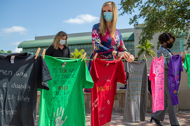 Photo shows FGCU faculty hanging T-shirt